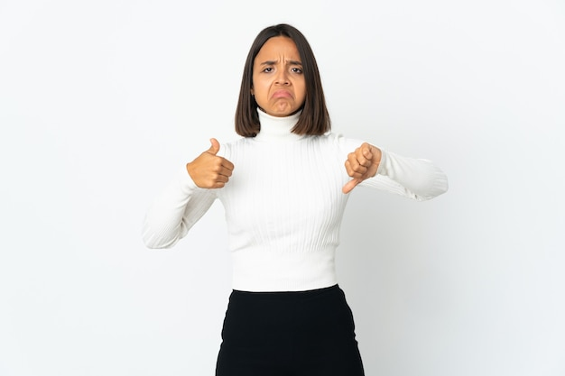 Young latin woman isolated on white wall making good-bad sign. undecided between yes or not