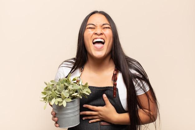 Молодая латинская женщина громко смеется над какой-то веселой шуткой, чувствует себя счастливой и веселой, веселится
