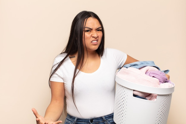 Young latin woman looking angry, annoyed and frustrated screaming wtf