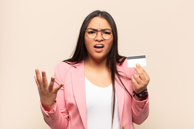Young latin woman looking angry, annoyed and frustrated screaming