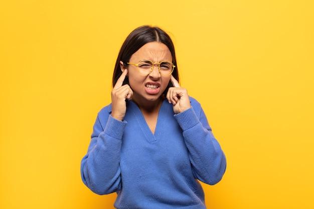 怒り、ストレス、イライラしているように見える若いラテン女性は、耳をつんざくような音、音、または大音量の音楽で両耳を覆っています