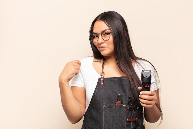 Молодая латинская женщина выглядит высокомерной, успешной, позитивной и гордой, указывая на себя