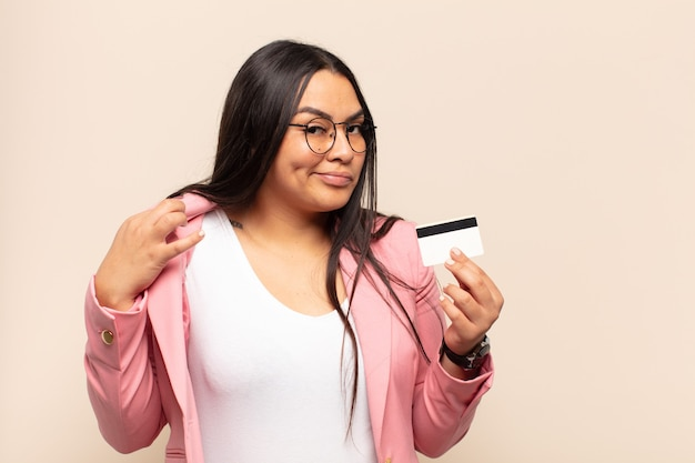 Young latin woman looking arrogant, successful, positive and proud, pointing to self
