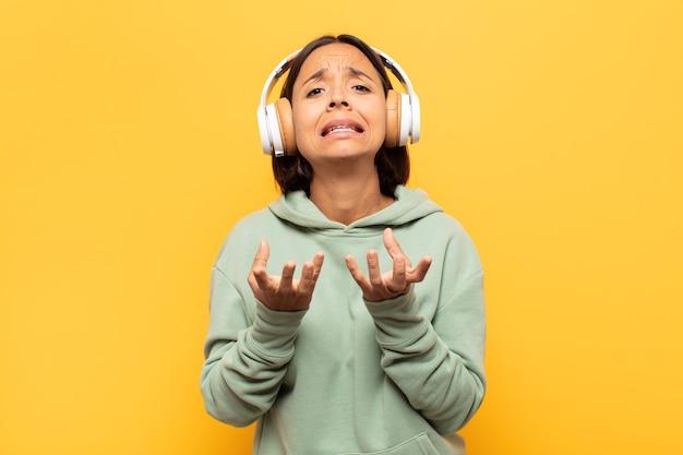 絶望的でイライラし、ストレスを感じ、不幸でイライラし、叫び、悲鳴を上げている若いラテン女性