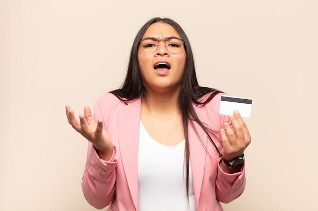 Молодая латинская женщина выглядит отчаянной и разочарованной, подчеркнутой, несчастной и раздраженной, кричит и кричит