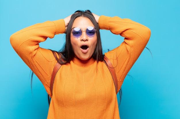 興奮して驚いた若いラテン女性は、両手を頭に向けて口を開け、幸運な勝者のように感じています