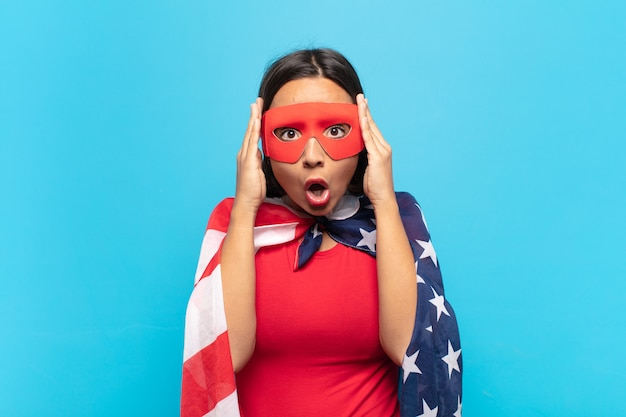 Молодая латинская женщина, выглядящая взволнованной и удивленной, с открытым ртом и обеими руками за голову, чувствуя себя счастливым победителем