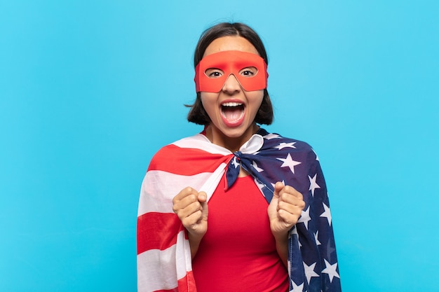 Молодая латинская женщина выглядит очень счастливой и удивленной, празднует успех, кричит и прыгает