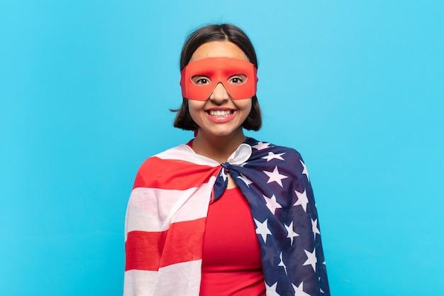 広く、楽しく、ルーニーな笑顔と目を大きく開いて幸せで間抜けに見える若いラテン女性 Premium写真