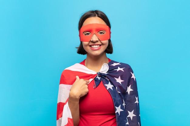 Молодая латинская женщина выглядит гордой, уверенной и счастливой, улыбается и указывает на себя или делает знак номер один