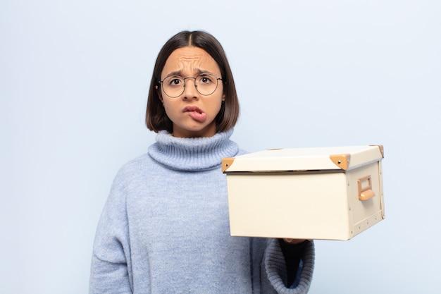 Молодая латинская женщина выглядит озадаченной и сбитой с толку, прикусывает губу нервным жестом, не зная ответа на проблему
