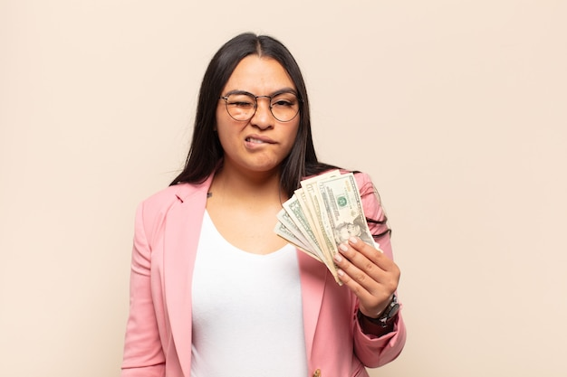 Young latin woman looking puzzled and confused, biting lip with a nervous gesture, not knowing the answer to the problem