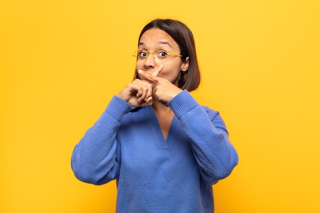 真面目で不機嫌そうな若いラテン女性が両指を前に交差させて拒絶し、沈黙を求めた