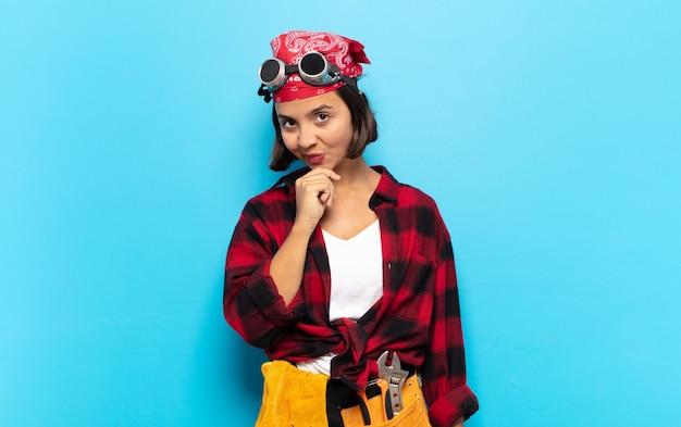 Молодая латинская женщина выглядит серьезной, сбитой с толку, неуверенной и задумчивой, сомневающейся среди вариантов или вариантов