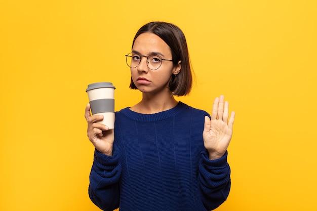 Молодая латинская женщина выглядит серьезной, строгой, недовольной и сердитой, показывая открытую ладонь, делая жест стоп