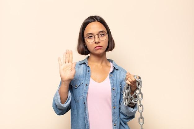 真剣で、厳しく、不快で、怒っているように見える若いラテン女性は、手のひらを広げて停止のジェスチャーをしている