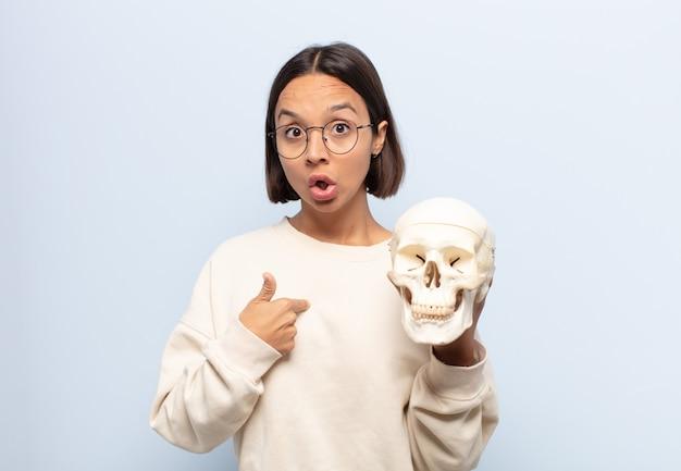 충격과 입 벌리고 놀란 찾고 젊은 라틴 여자, 자기를 가리키는