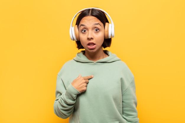 ショックを受けて驚いた若いラテン女性が口を大きく開いて、自分を指しています