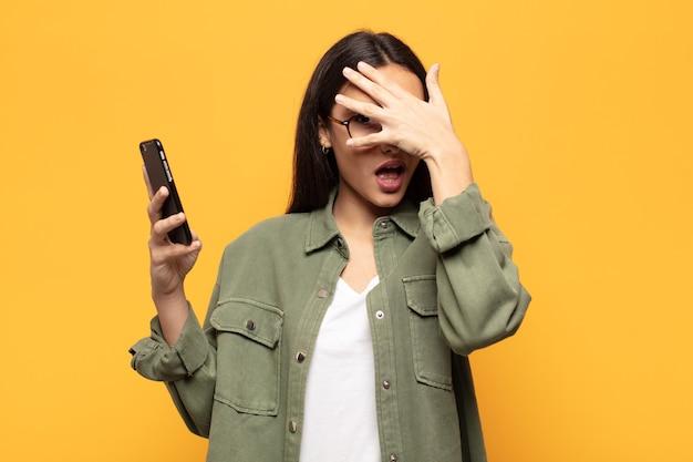Молодая латинская женщина выглядит шокированной, напуганной или напуганной, закрывает лицо рукой и заглядывает между пальцами