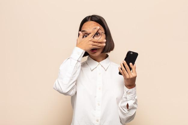 충격, 무서워 또는 겁에 질린 젊은 라틴 여자, 손으로 얼굴을 덮고 손가락 사이 엿보기