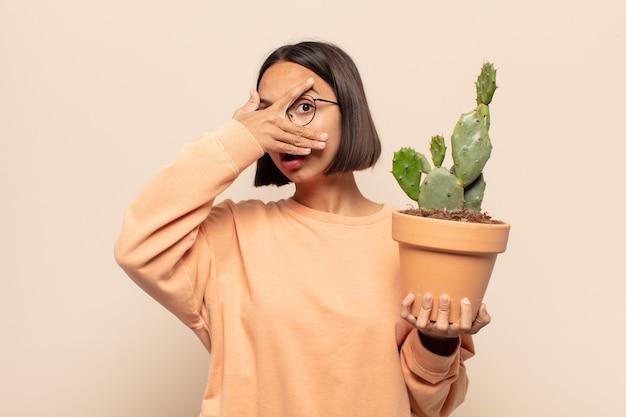 충격, 무서움 또는 겁에 질린 젊은 라틴 여자, 손으로 얼굴을 덮고 손가락 사이 엿보기