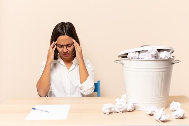 ストレスと欲求不満を見て、頭痛でプレッシャーの下で働いて、問題に悩まされている若いラテン女性