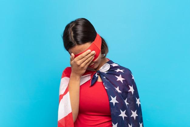 Молодая латинская женщина, которая выглядит напряженной, пристыженной или расстроенной, с головной болью, закрывает лицо рукой