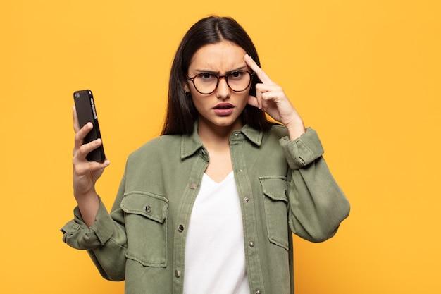 Молодая латинская женщина выглядит удивленной, с открытым ртом, шокированной, осознающей новую мысль, идею или концепцию