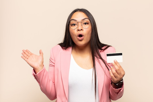 Young latin woman looking surprised and shocked, with jaw dropped holding an object with an open hand on the side