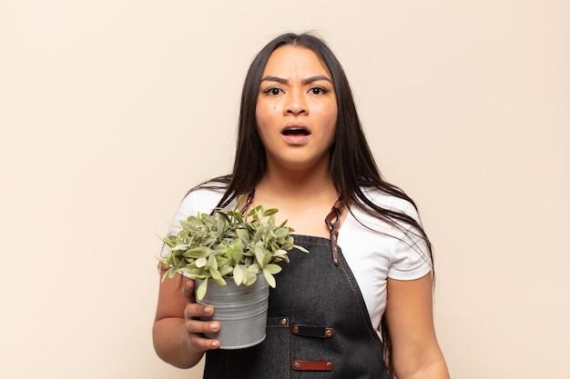 Молодая латинская женщина выглядит очень шокированной или удивленной, смотрит с открытым ртом и говорит:
