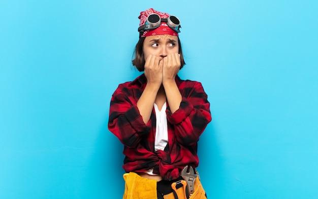 Молодая латинская женщина выглядит обеспокоенной, встревоженной, напряженной и испуганной, кусает ногти и смотрит в пространство для боковой копии