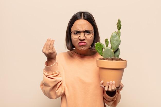 あなたの借金を支払うようにあなたに言って、capiceまたはお金のジェスチャーをしている若いラテン女性!