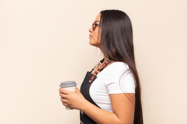 Молодая латинская женщина на виде профиля, желающая скопировать пространство впереди, думает, воображает или мечтает