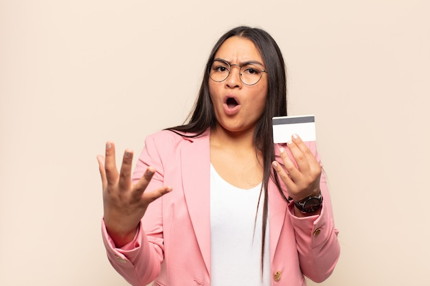Young latin woman open-mouthed and amazed, shocked and astonished with an unbelievable surprise