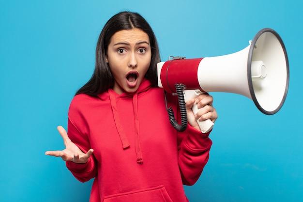若いラテン女性は口を開けて驚いて、ショックを受けて、信じられないほどの驚きに驚いた