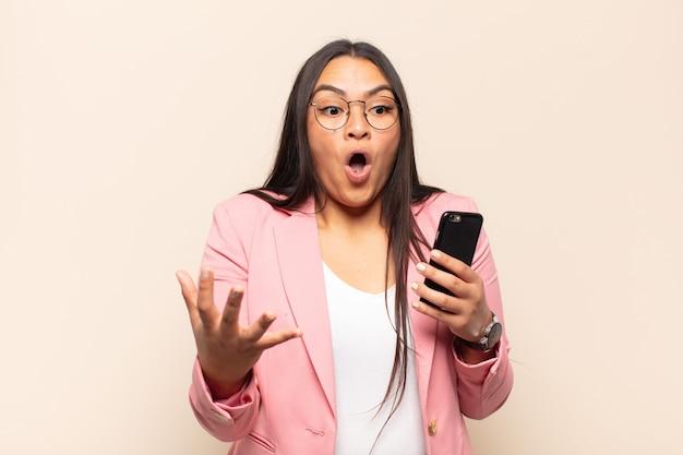 Молодая латинская женщина с открытым ртом изумлена, потрясена и удивлена невероятным сюрпризом