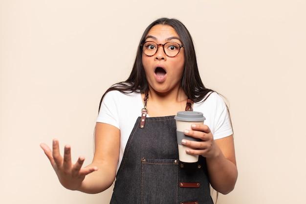 젊은 라틴 여성은 입을 벌리고 놀랐고 놀랍고 놀라움에 놀라움을 금치 못했습니다.