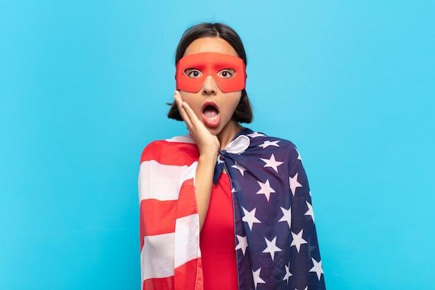 ショックと不信に口を開けた若いラテン系女性、頬に手を当て、腕を組んで、愚かで驚いた。