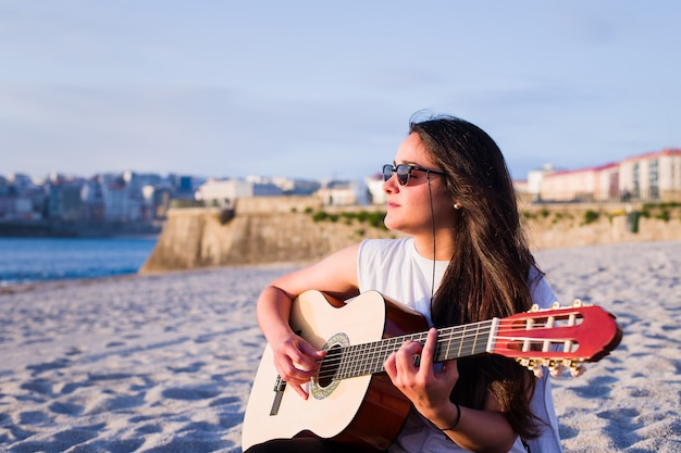 Young latin woman play acoustic guitar on the corunna beach in galicia, spain.