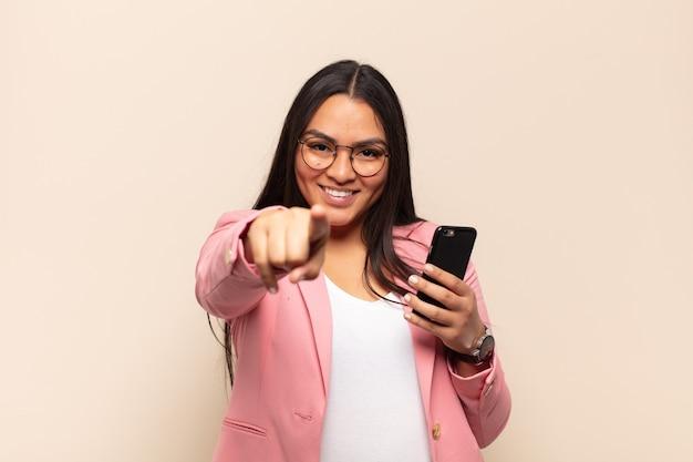 満足、自信を持って、フレンドリーな笑顔でカメラを指して、あなたを選ぶ若いラテン女性