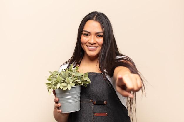 Молодая латинская женщина с довольной, уверенной, дружелюбной улыбкой указывая на камеру, выбирая вас