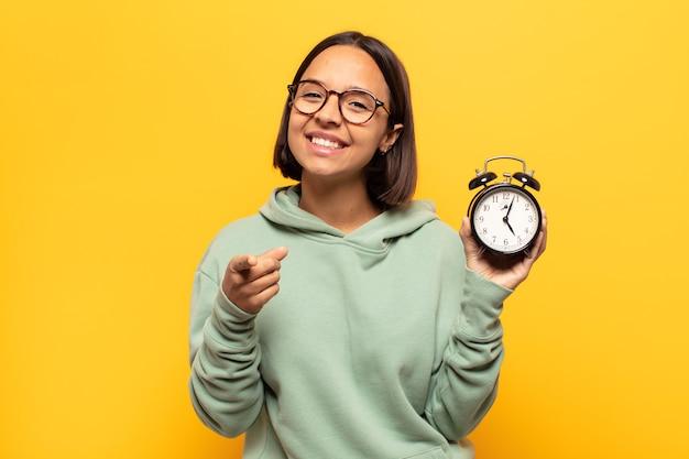만족, 자신감, 친절한 미소로 카메라를 가리키는 젊은 라틴 여자, 당신을 선택