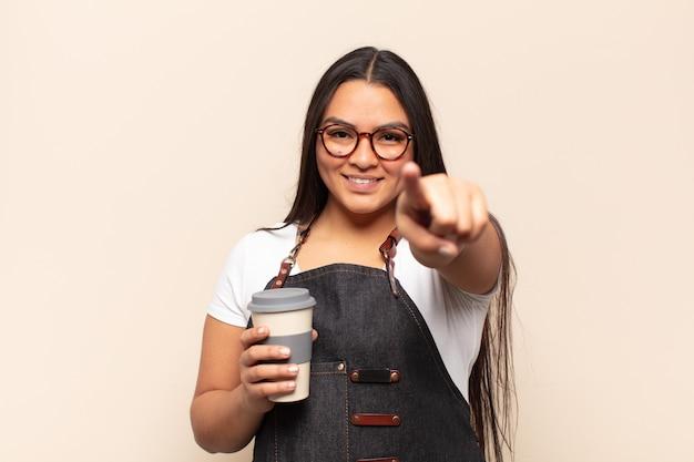 Молодая латинская женщина с довольной, уверенной, дружелюбной улыбкой указывает на камеру