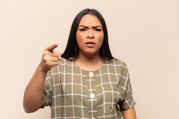 Молодая латинская женщина, указывающая на камеру с сердитым агрессивным выражением лица, похожая на разъяренного, сумасшедшего босса