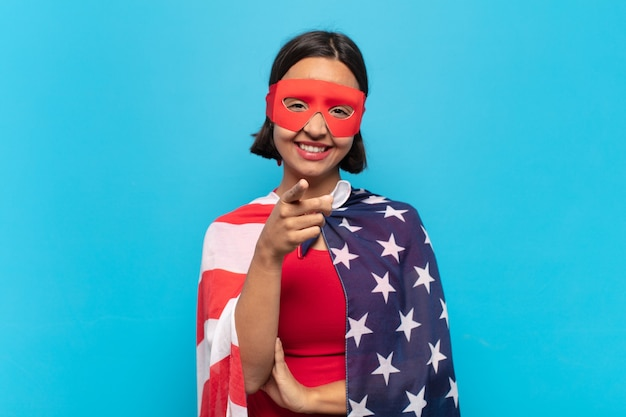 Молодая латинская женщина с довольной, уверенной, дружелюбной улыбкой указывая вперед, выбирая вас