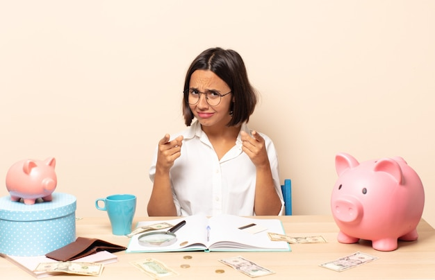 Молодая латинская женщина, указывая вперед на камеру обоими пальцами и сердитым выражением лица, говорит вам выполнять свой долг
