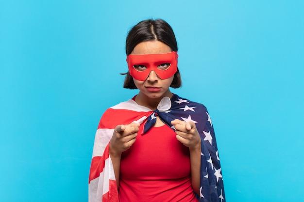 손가락과 화난 표정으로 카메라를 향해 앞으로 가리키는 젊은 라틴 여자, 당신의 의무를 다하라고 말합니다.