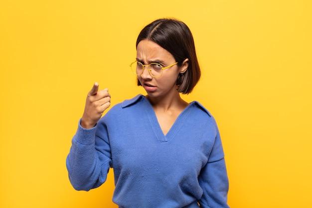 분노, 미친 보스처럼 보이는 화가 공격적인 표정으로 가리키는 젊은 라틴 여자