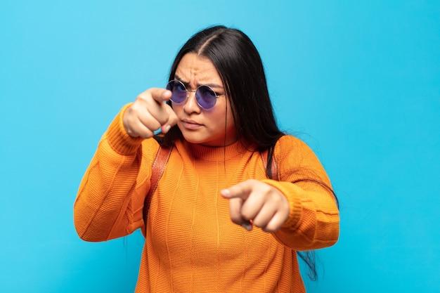 손가락과 화난 표정으로 가리키는 젊은 라틴 여자, 의무를 다하라고 말함