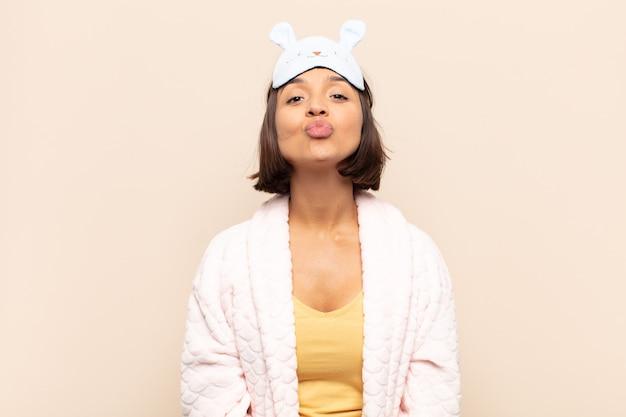 かわいい、楽しく、幸せで、素敵な表情で唇を押して、キスを送る若いラテン女性